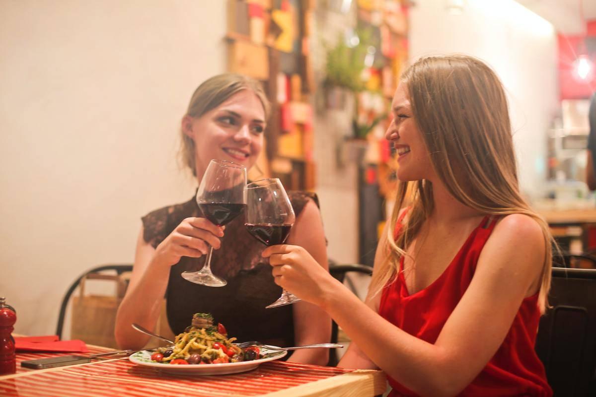 women touching wine glasses over dinner