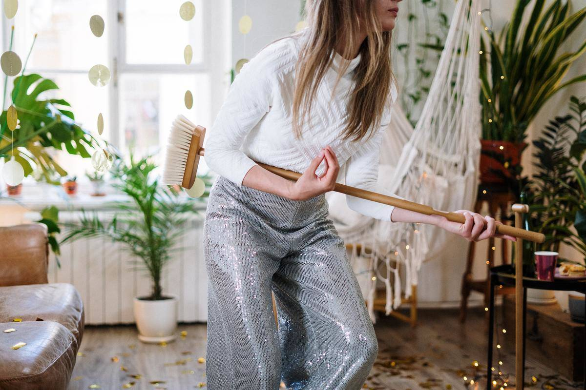woman in silver sparkly pants using broom as fake guitar