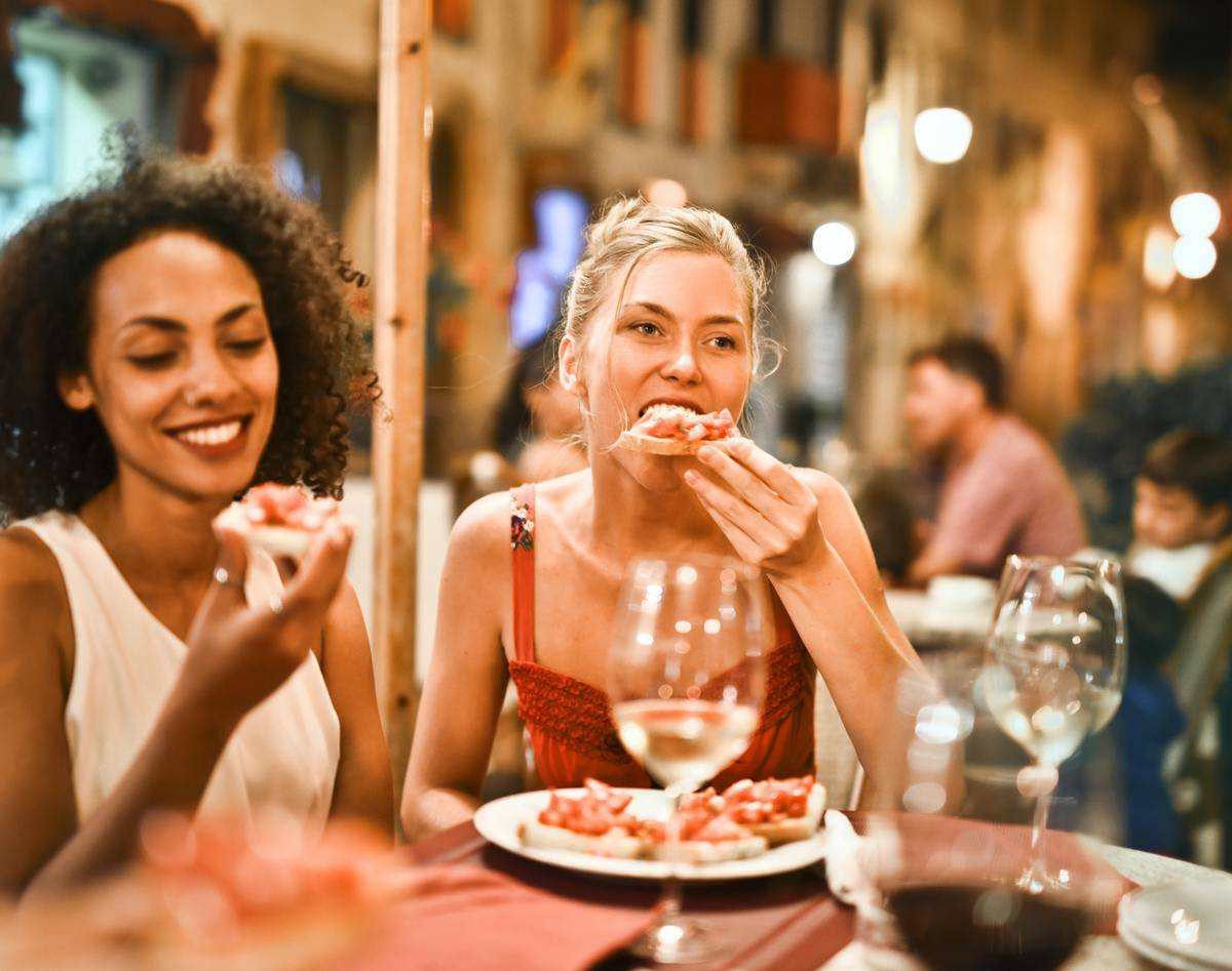 woman eating pizza at patio
