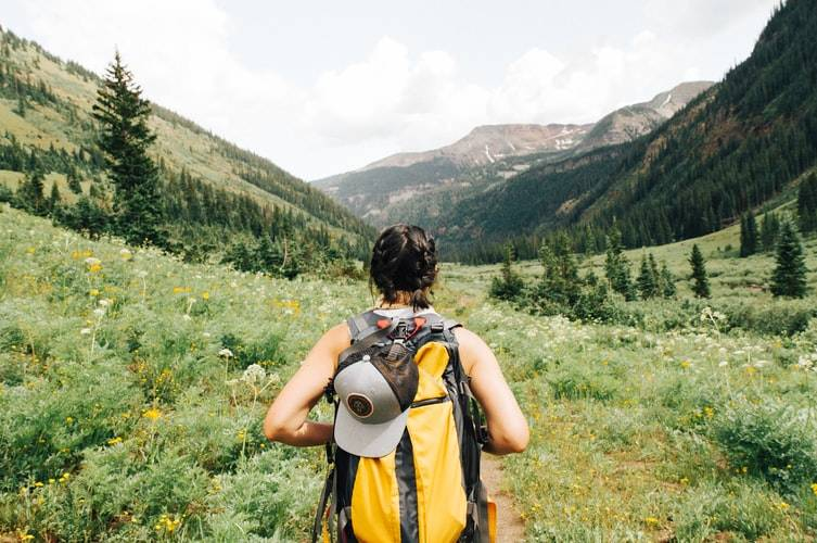 Behind shot of woman hiking with large backpack