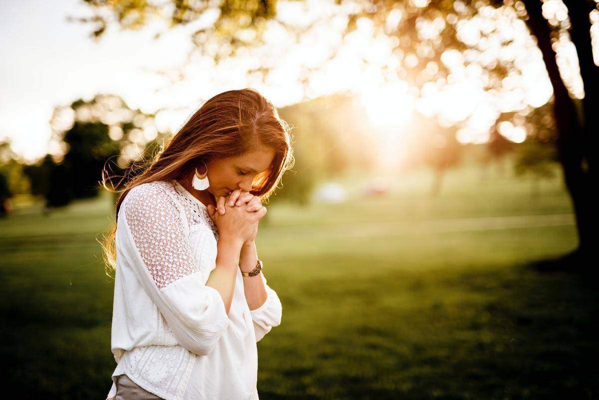 woman praying in a park for hope