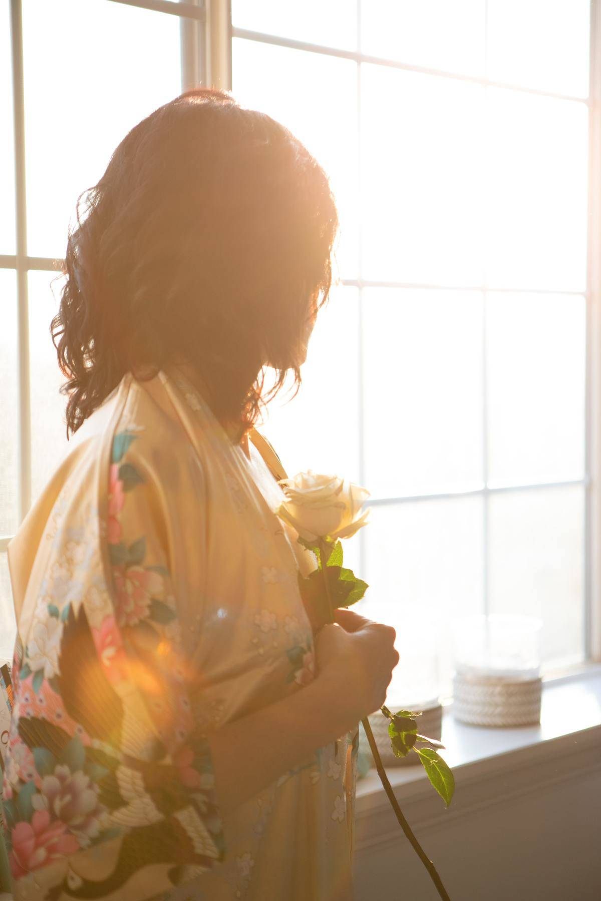 woman holding rose and looking out the window in sunlight