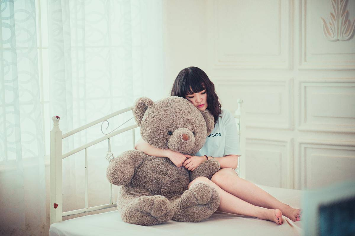 woman hugging giant teddy bear in bed