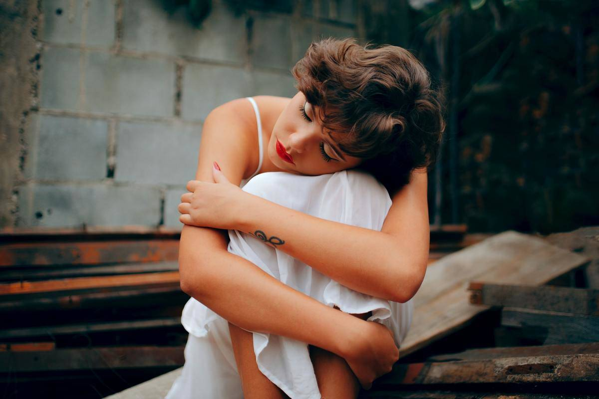 woman hugging her knee in sadness by brick wall