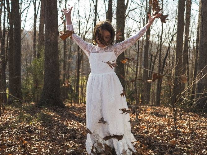 Woman in a forest wearing a long white dress throwing leaves all around herself