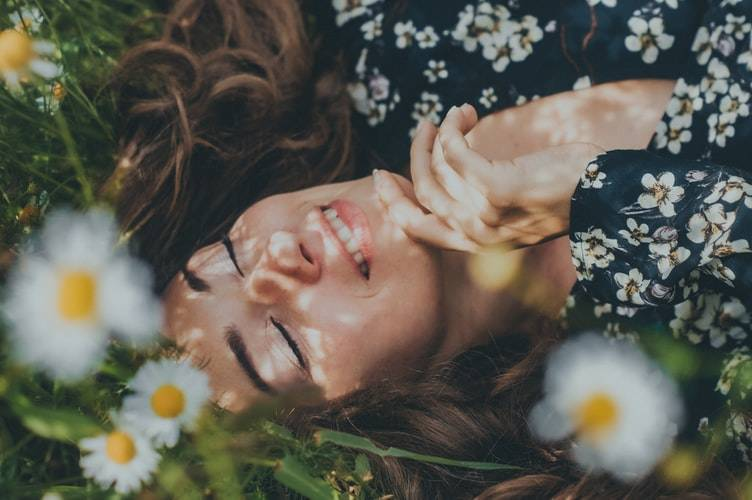 woman smiling and laying in bed of flowers