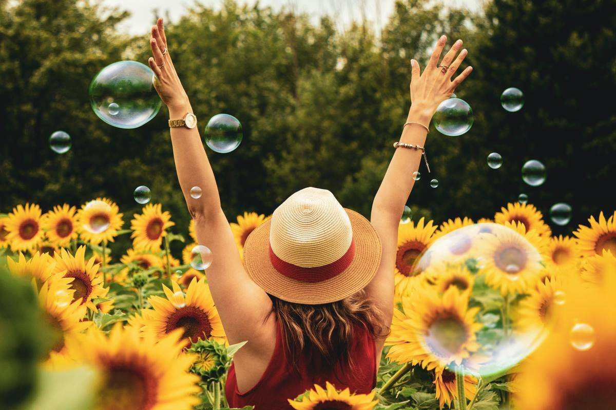woman in straw hat in field of sunflowers with bubbles