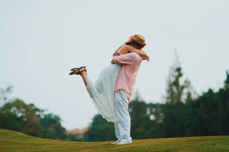 couple embracing outdoors and the woman has her arms around the man's neck and her legs up