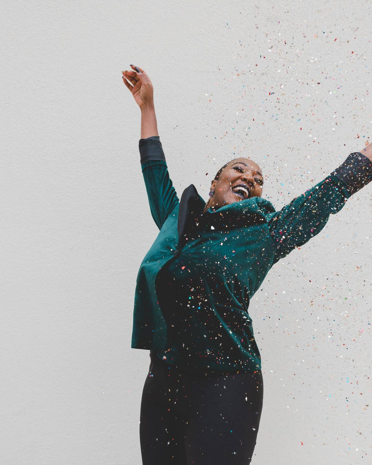 woman jumping with confetti and smiling