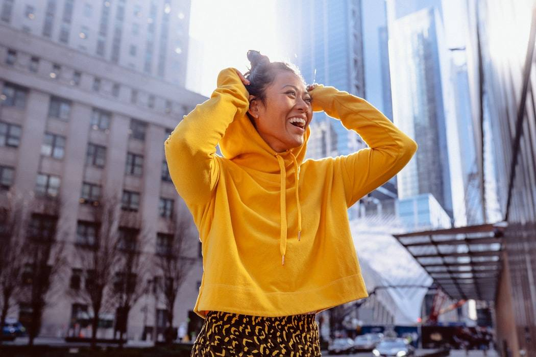 woman smiling in yellow hoodie downtown