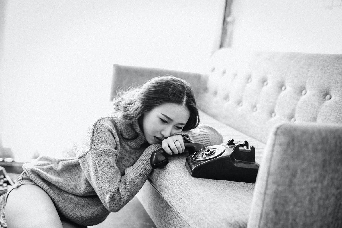 woman laying by the phone in sadness (black and white photo)
