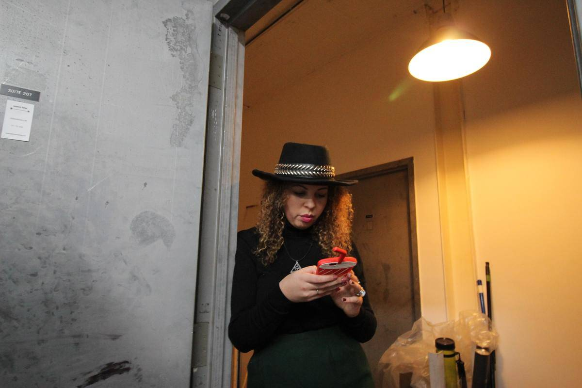 woman with black hat leaning against doorway looking at phone