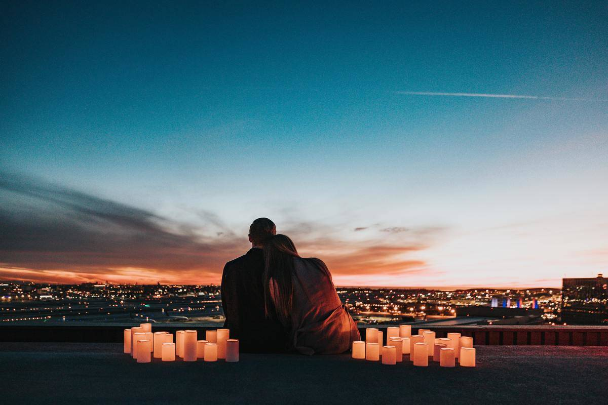 woman leaning on man's shoulder watching the sunset and surrounded by candles