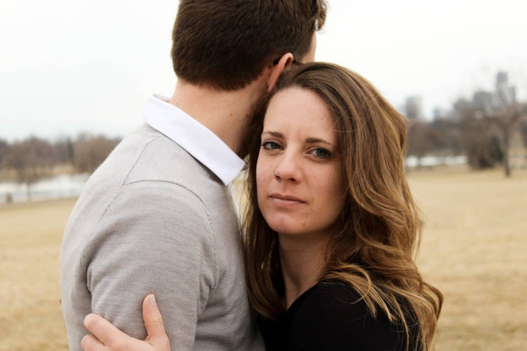 woman staring at camera looking unhappy as she holds a man who's staring the other way