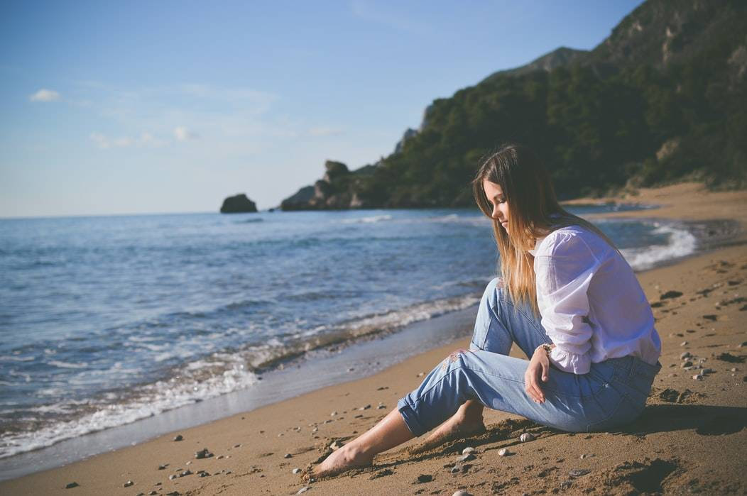 woman sitting on the beach in jeans staring at the sand