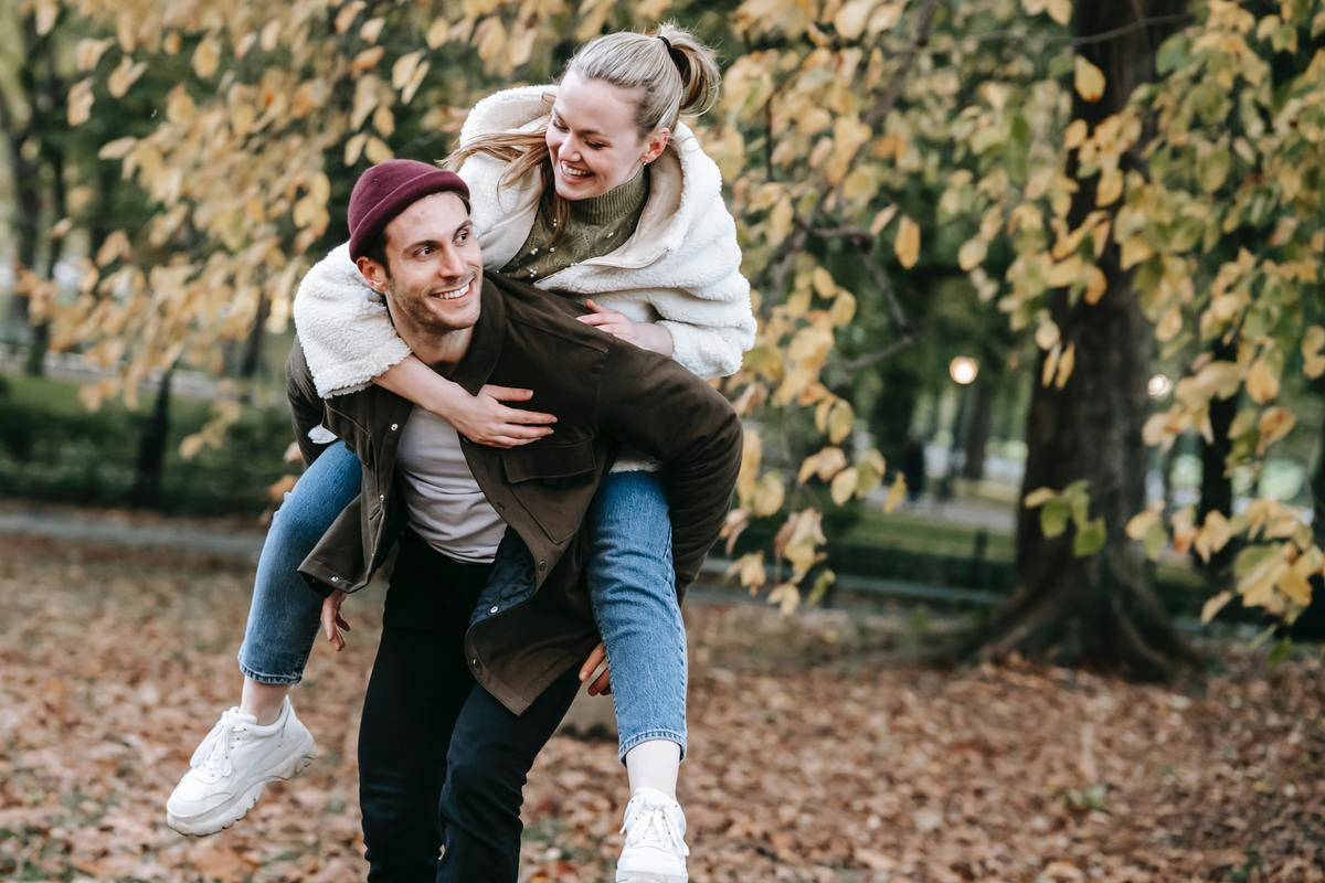 woman piggy backs on man shoulders