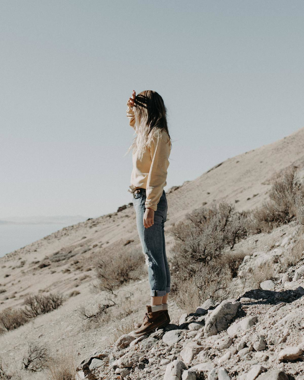 woman standing on rocks hiding her face