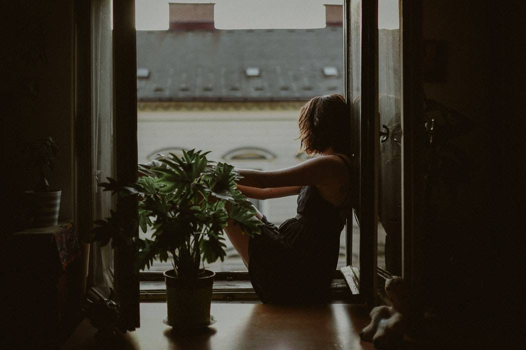 Side shot of woman sitting by window staring out at the view