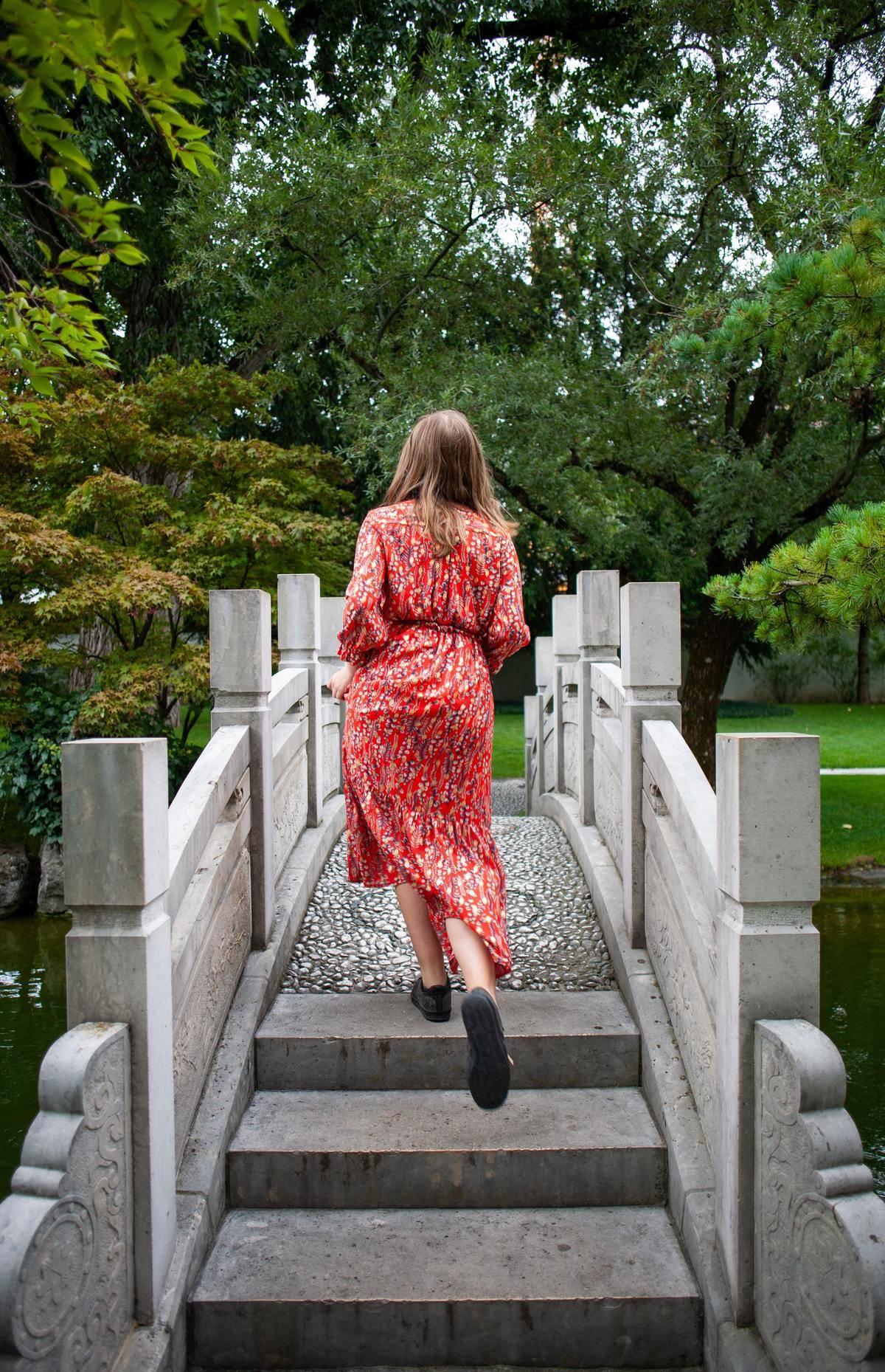 woman swaying her hips as she walks across a bridge