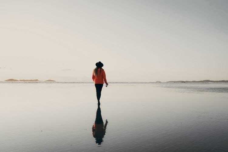 woman walking in shallow water on a beach