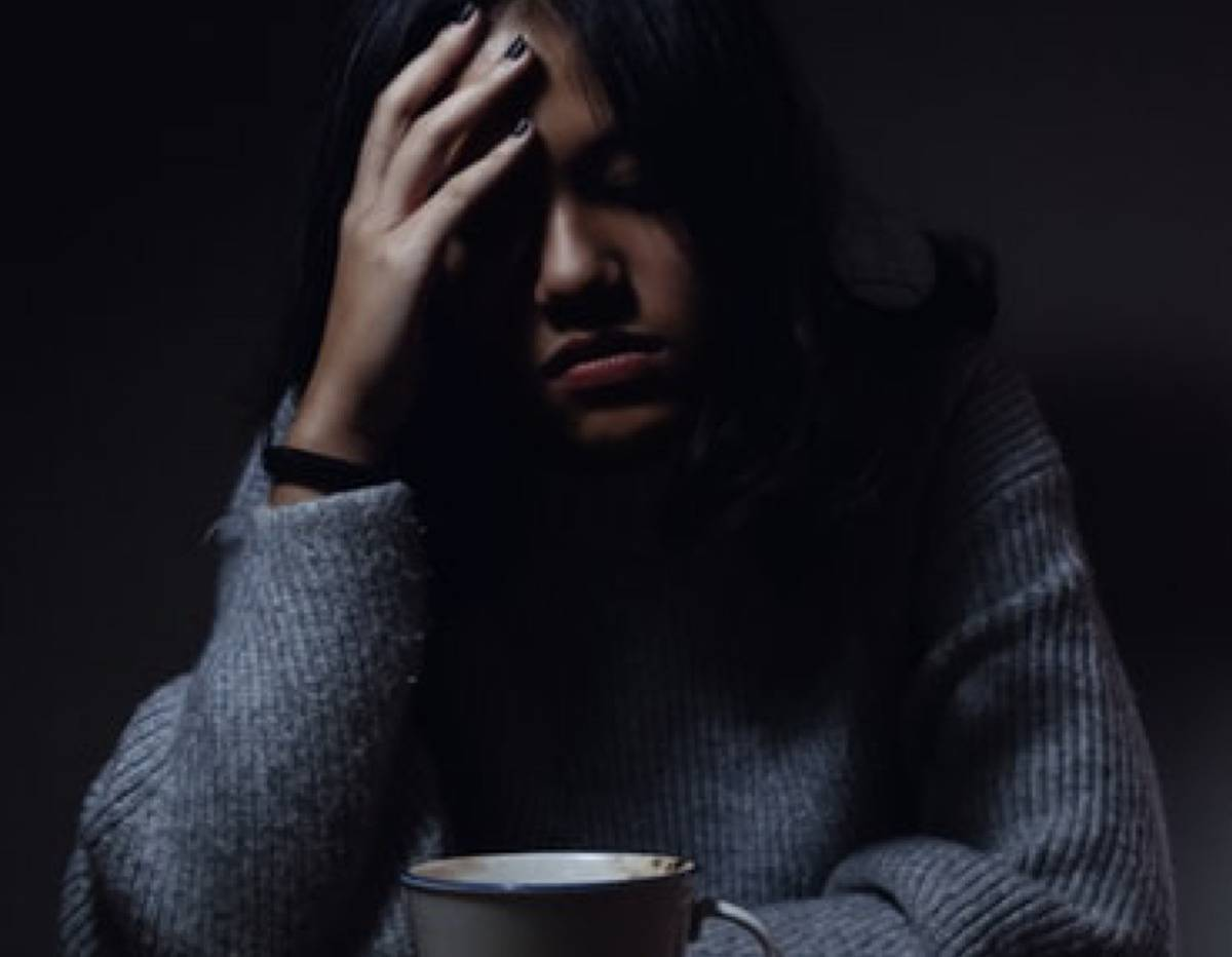 woman with her head in her hands as she drinks coffee