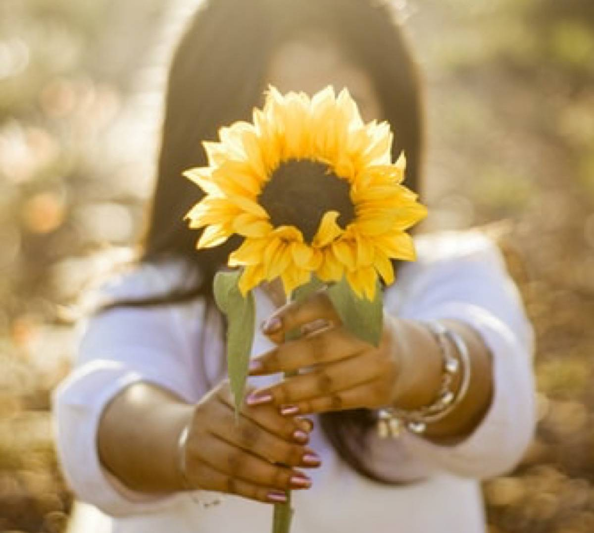 woman with sunflower in front of her face posing in front of camera