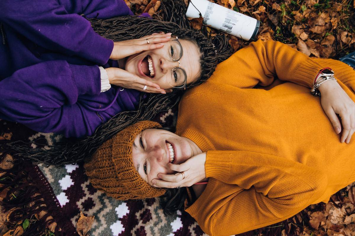 women laughing on blanket sitting across each other
