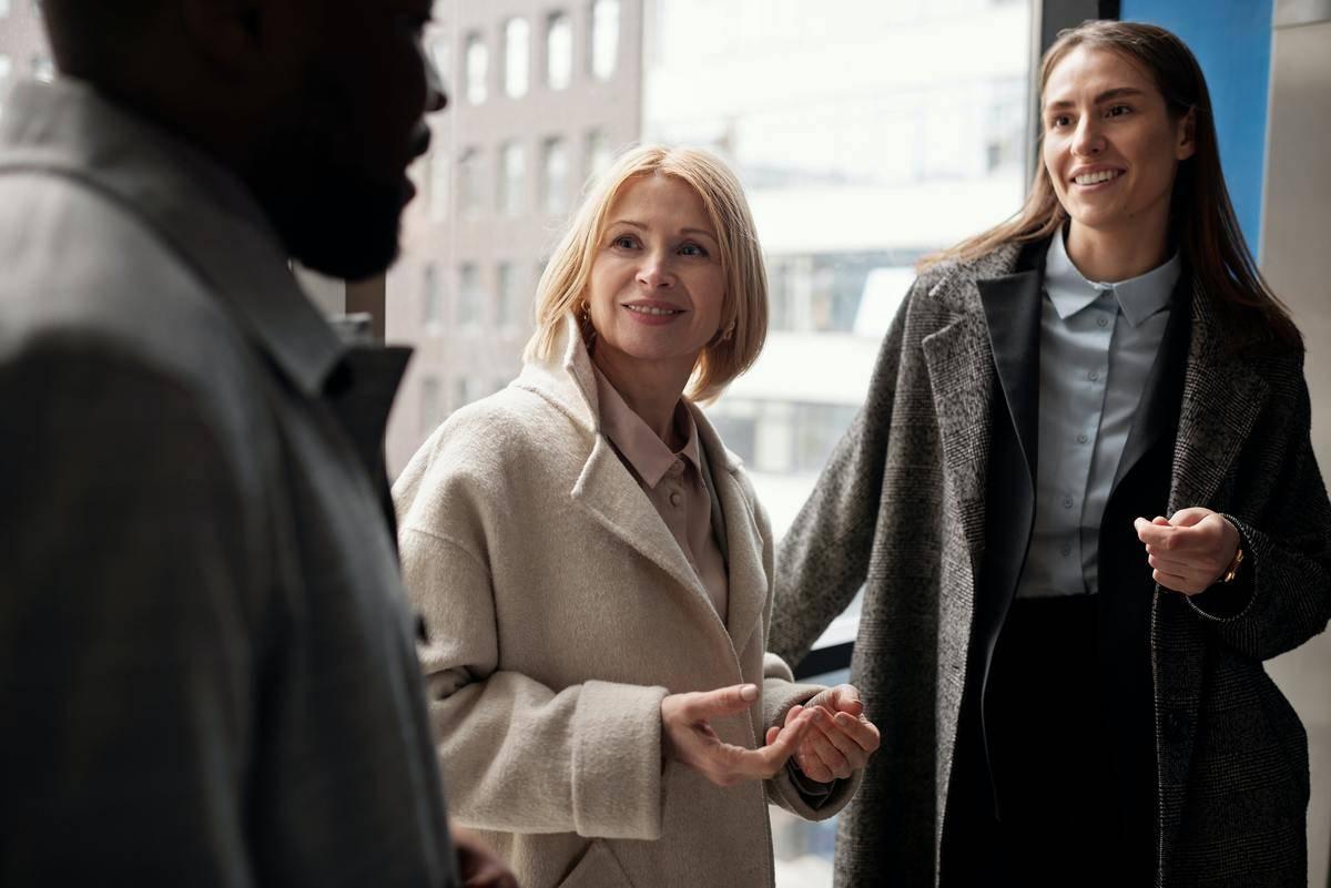 two women talking to man outside