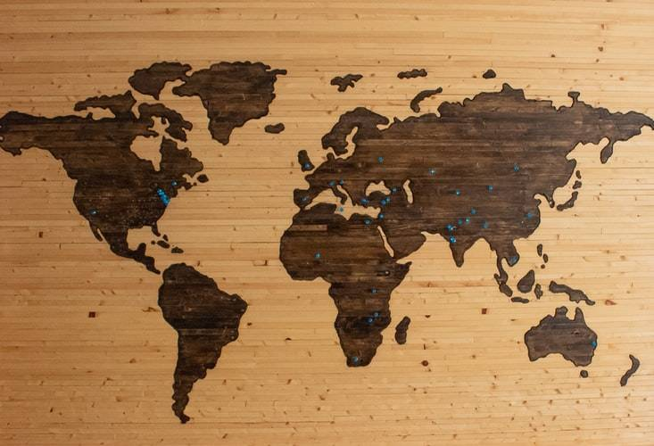wooden replica of the world map with pushpins inside of it