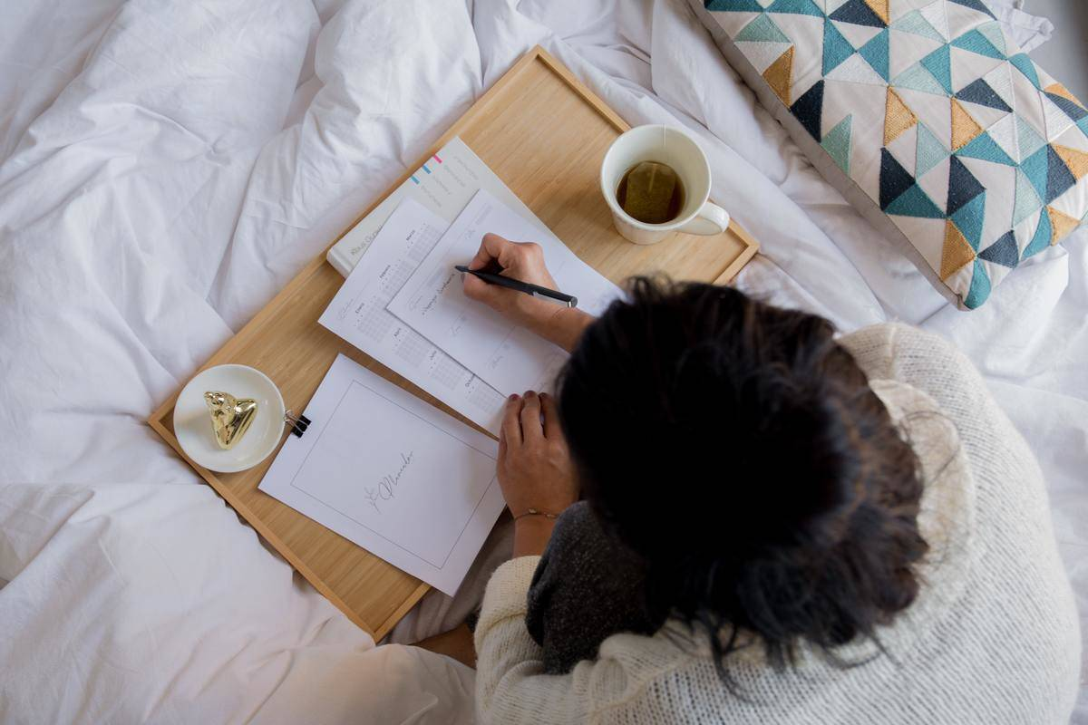 woman making notes writing on bed desk