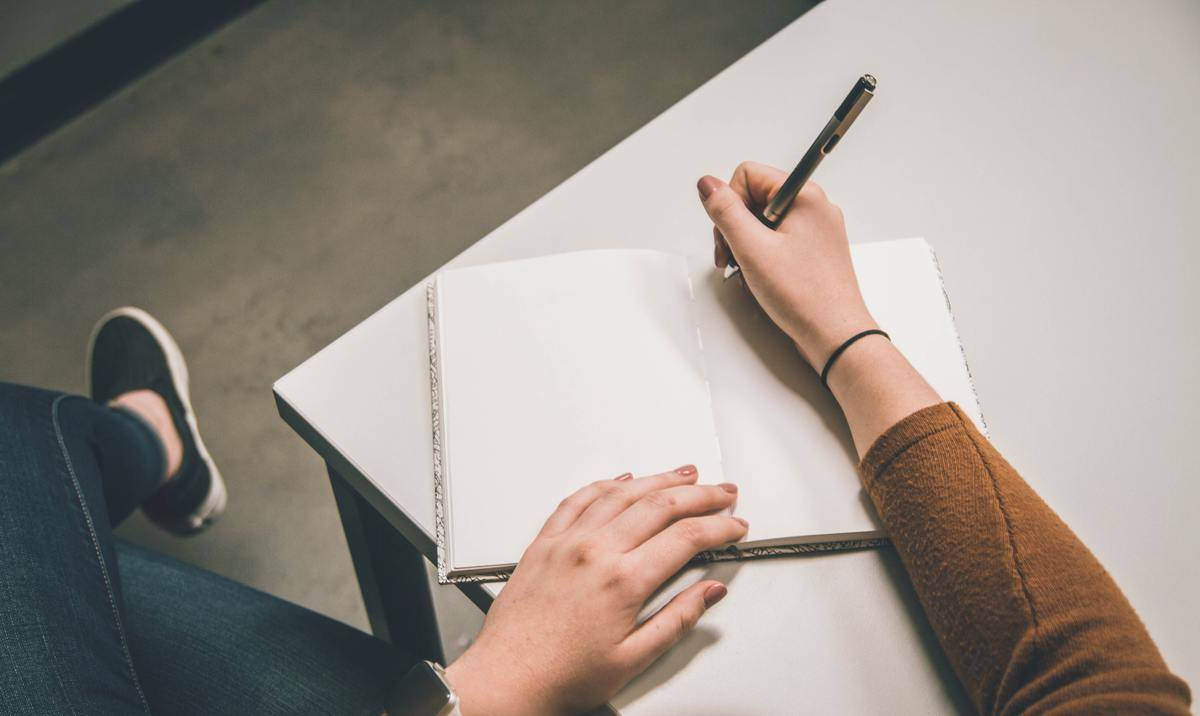 hand holding a pen and writing in a journal