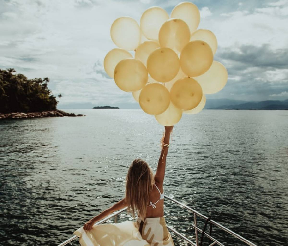 woman on boat with bunch of balloons in her hand