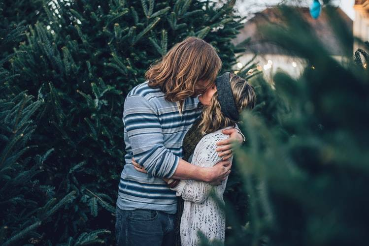 couple kissing passionately against a bunch of christmas trees