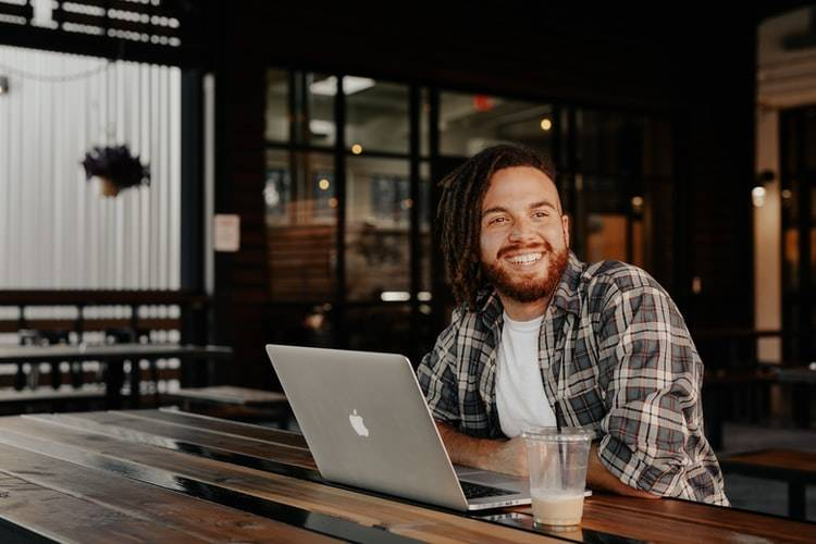 man at coffee shop smiling at something off camera with his macbook computer open in front of him