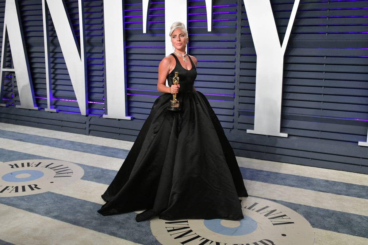 Lady Gaga in a stunning black dress posing with her award, winner of the Music (Original Song) award for 'Shallow' from 'A Star Is Born,' attends the 2019 Vanity Fair Oscar Party