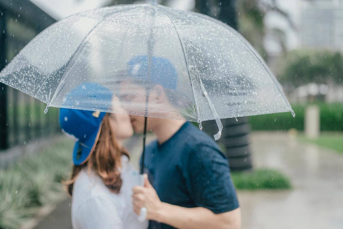 Man and woman kiss under umbrella