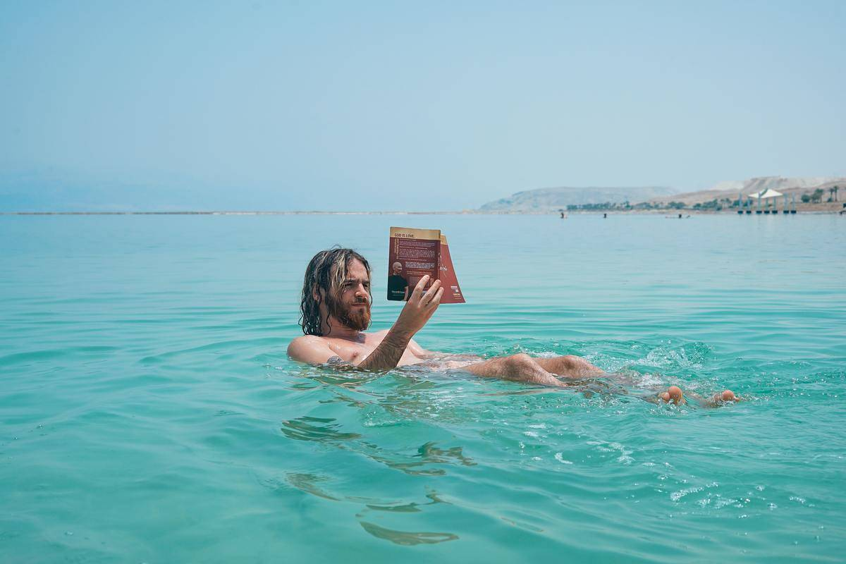 Man reading in water ocean