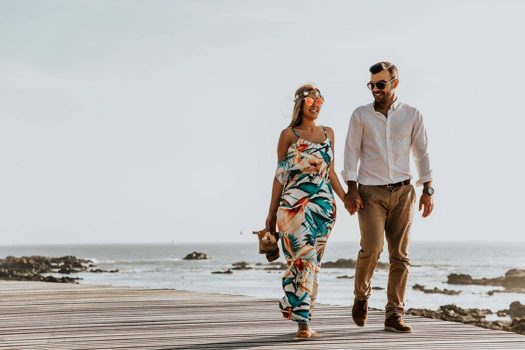 couple walking on a boardwalk and smiling