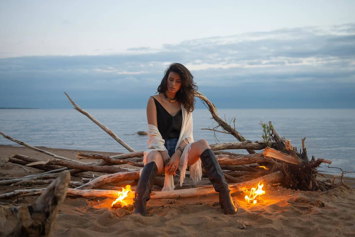 Woman sitting on log between two flames