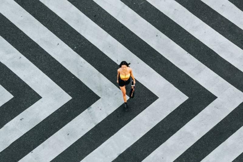 Birds-eye view of woman walking on black and white striped sidewalk