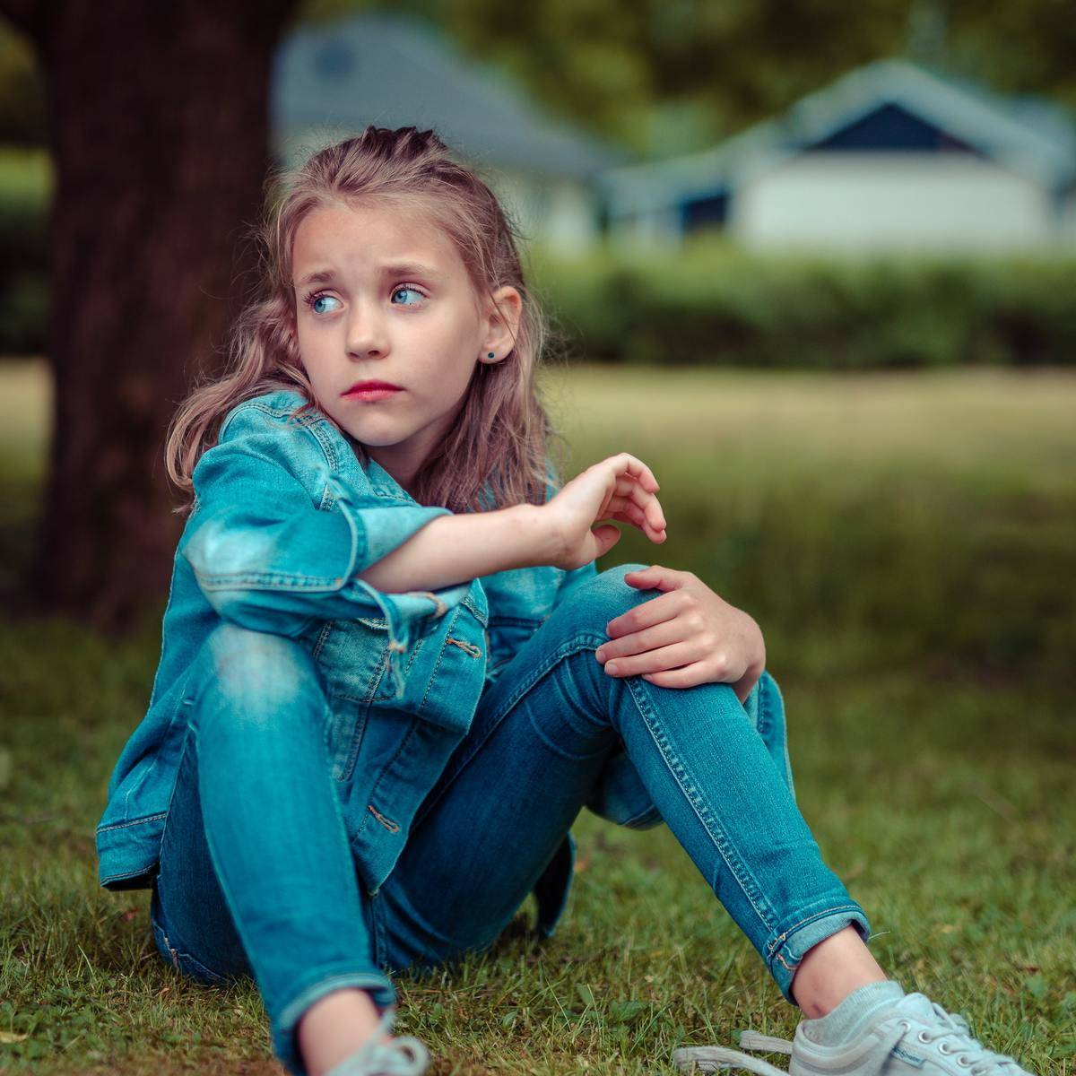 Young Girl Sits On Grass looking to the side