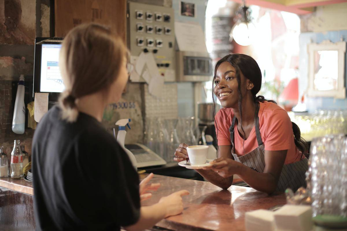 barista handing coffee to customer