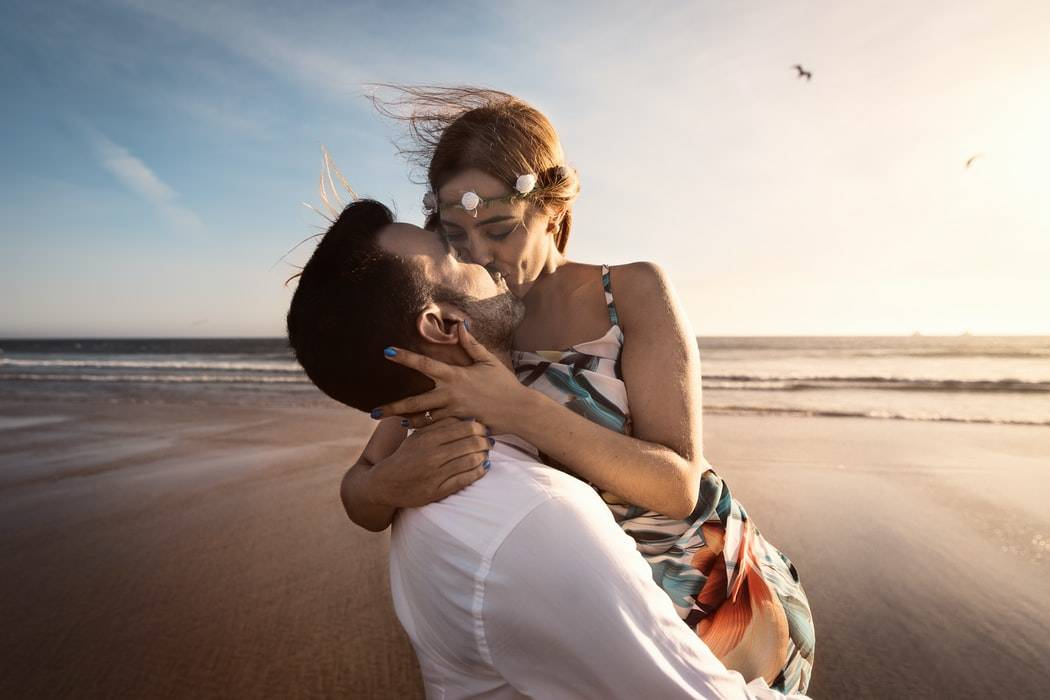 man and woman kissing on the beach