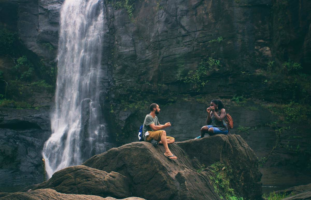 couple on rocks in front of waterfall