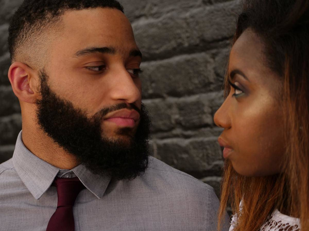 man and woman looking into each other's eyes with serious expressions