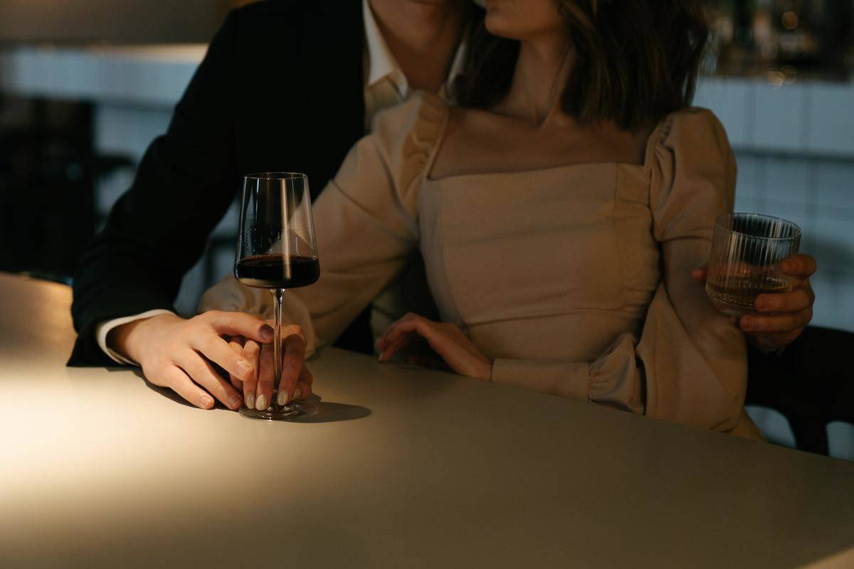 man and woman leaning into each other at table