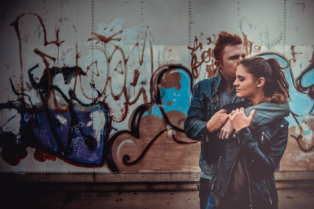 couple in leather jackets embracing outside