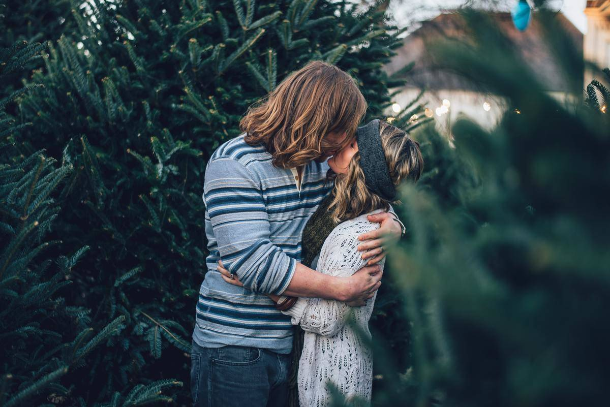 couple kissing in front of pine tree