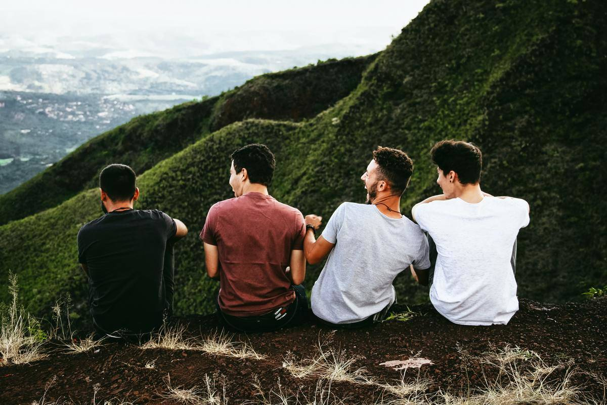 group of four men sitting on cliff