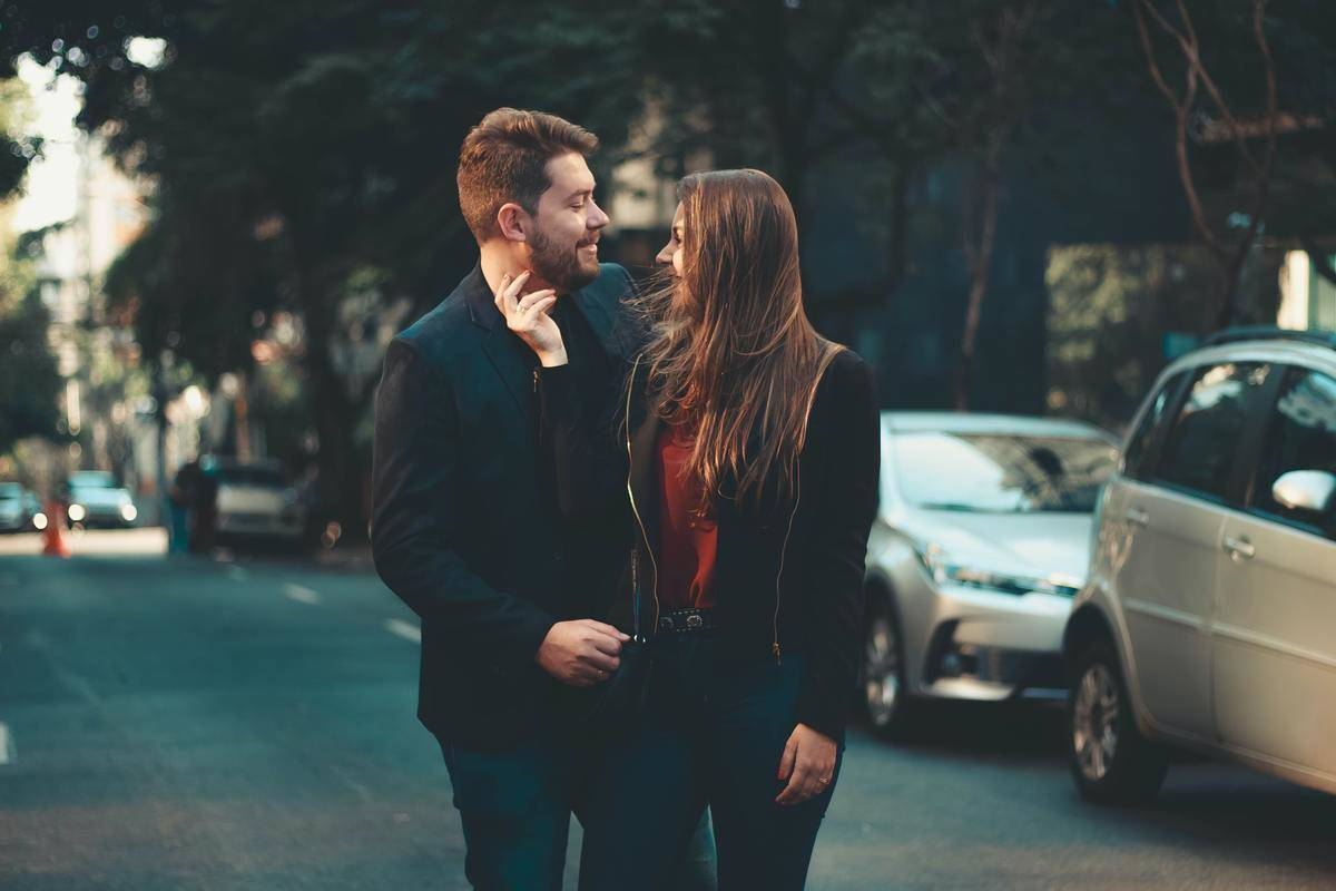 woman touching man's face on street smiling